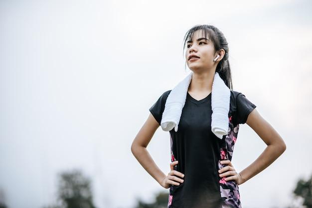 Женщина стоя расслабьтесь после тренировки.