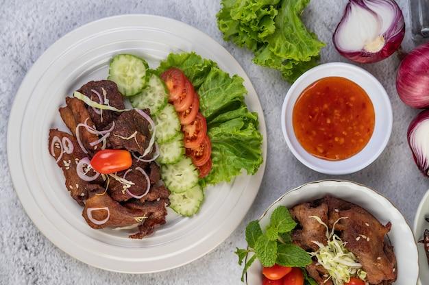 Жареная свинина с кунжутом в белом блюде.