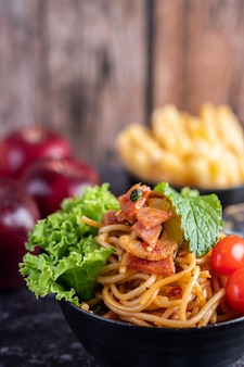 Спагетти в черной чашке с помидорами и листьями салата.