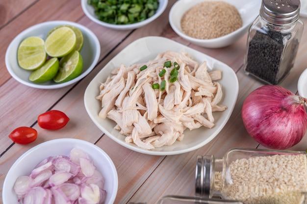 ゆで鶏肉を木製のテーブルの白い皿に粉々に切る。