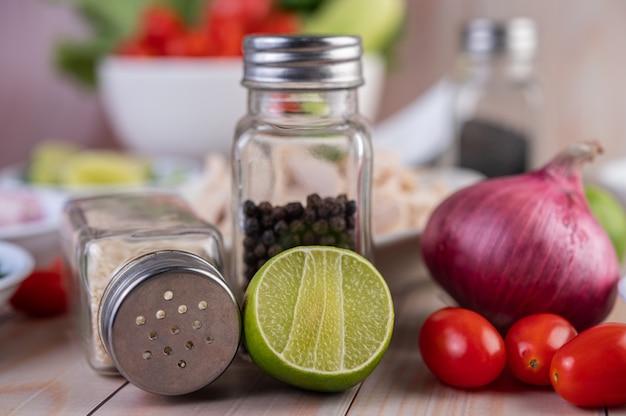ハーフカットレモン、トマト、赤玉ねぎを木製のテーブルに配置