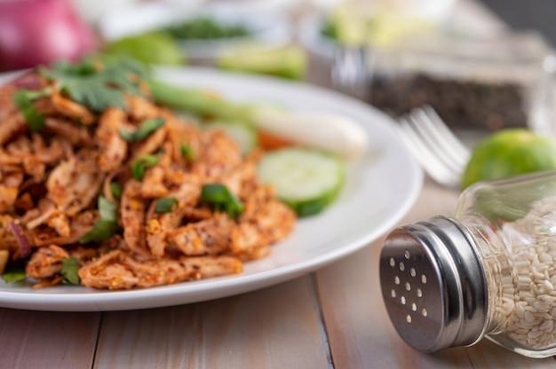 キュウリ、レタス、おかずが入った白い皿にスパイシーなひき肉。