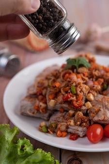 木製のテーブルの白いプレートにトマトとレタスでみじん切りにしたスパイシーな豚肉。