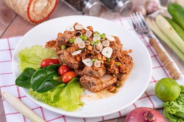 Пряный свинина, фарш с помидорами и листьями салата на белом фоне на деревянном столе.