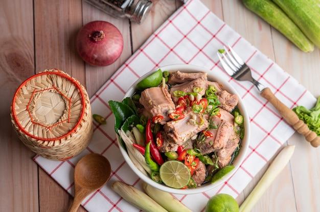 木製のテーブルの生地の部分に白いカップで茹でた豚カルビ。