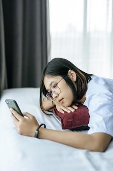 Женщина, одетая в белую рубашку, лежа на кровати и играя смартфон.