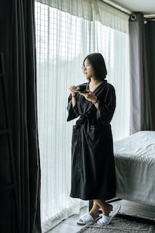 Женщины в черных халатах, раздают кофе в спальне.