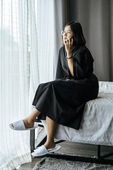 白いシャツを着て、ベッドに座って電話で話している女性。