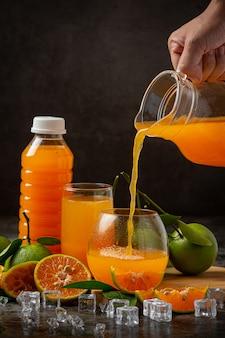 Стакан апельсинового сока и свежих фруктов на полу с кубиками льда.