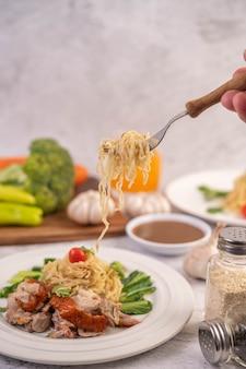 Спагетти на тарелке с помидорами кориандром и базиликом.
