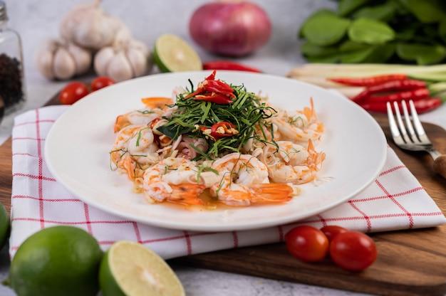 白い皿にエビのスパイシーサラダ。タイ料理。