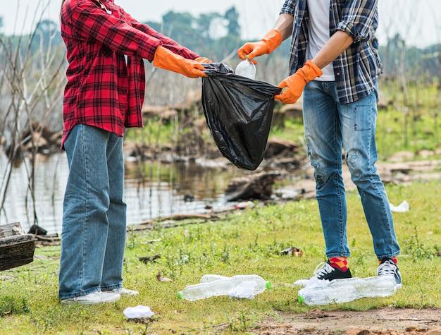 Мужчины и женщины помогают друг другу собирать мусор.
