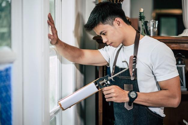 Плотник держит клей и прикрепляется к окну.