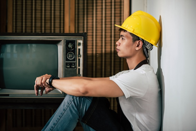 Механик одет в желтую шляпу и руки лежат на коленях.