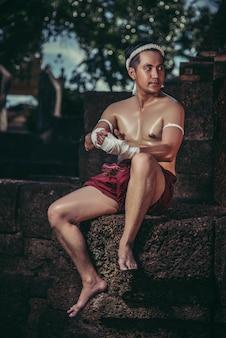 ボクサーは石の上に座って、テープを彼の手に結び、戦いの準備をしました。