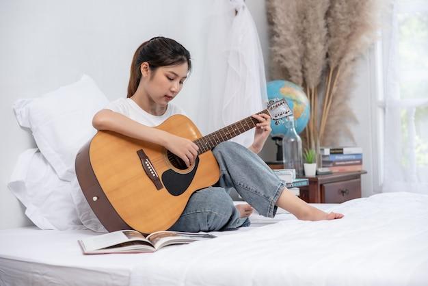 少女はベッドに座ってギターを弾いた。