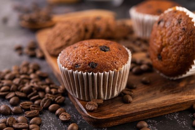 コーヒーの穀物が付いている木の皿に置かれるバナナのカップケーキ。