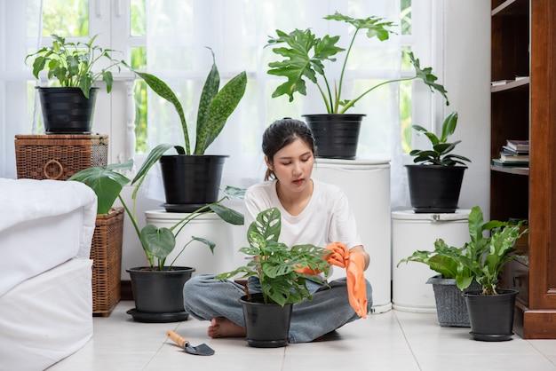 女性はオレンジ色の手袋を着用し、家に木を植えました。