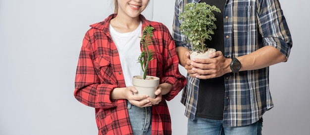 家に植木鉢を立って保持している男性と女性
