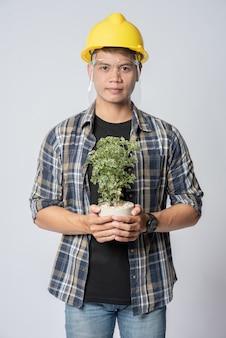 エンジニアリング帽子をかぶって、家に植木鉢を持って立っていた男。
