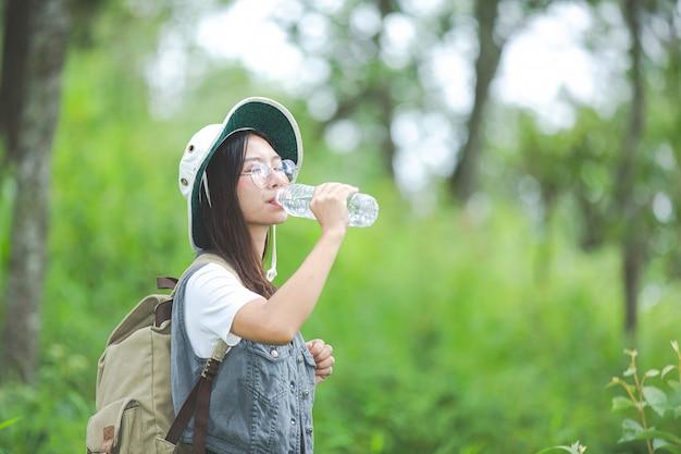 Счастливый турист гуляет по джунглям с рюкзаком.