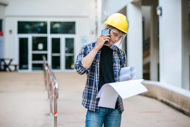 建築家は構内図を持ち、電話で話します。