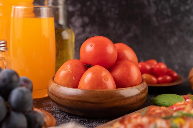 Свежие помидоры в деревянной чашке, виноград и апельсиновый сок в стакане.