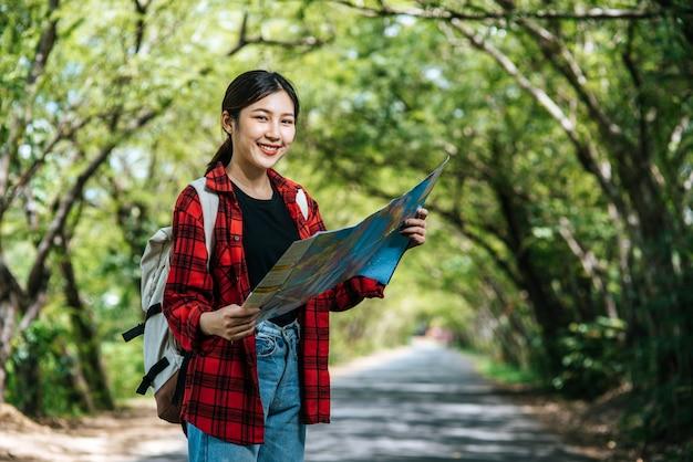 女性観光客が立ち、道路上の地図を見る。