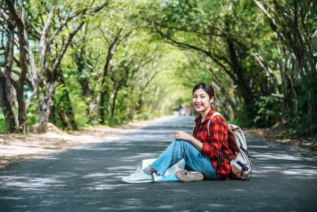 Женщины туристы несут рюкзак и сидят на дороге.