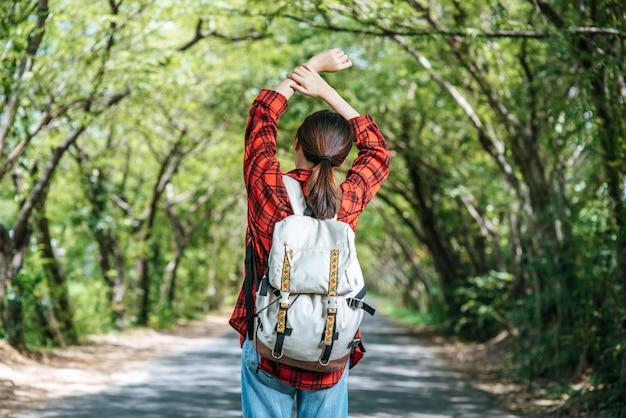 女性観光客がバックパックを背負って通りに立ちます。