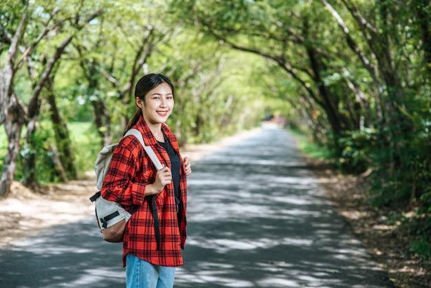 Женщины-туристы несут рюкзак и стоят на улице.