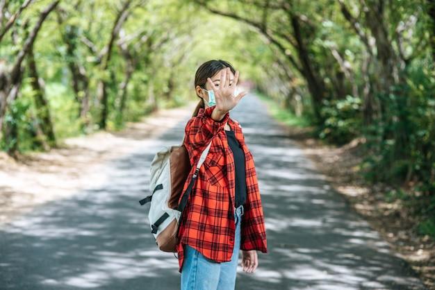Женщина турист, несущий рюкзак и поднимающий ее пять пальцев, чтобы запретить на дороге.
