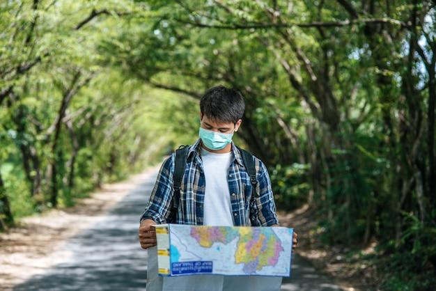 男性の観光客が立ち、道路上の地図を見てください。