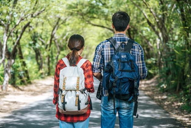 男性と女性の両方の観光客が道路上の地図を見に立っています。