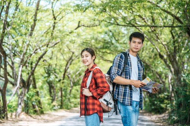 男性と女性の両方の観光客がバックパックを運び、お互いに向きを変えます。