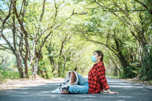 路上で座ってリラックスするマスクを身に着けている女性観光客。