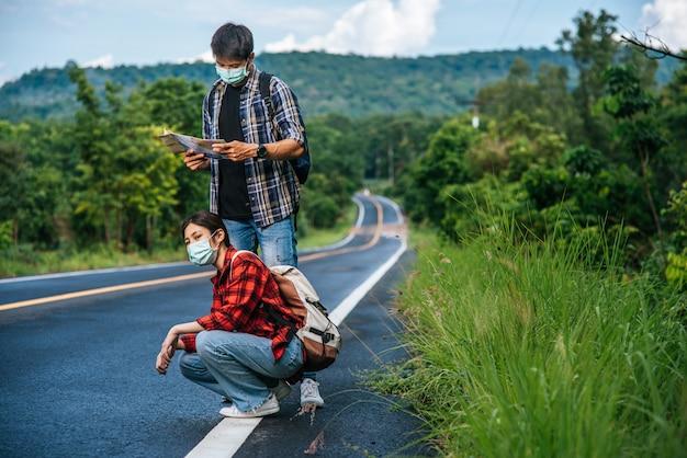 座っている女性の観光客、地図を見る男性の観光客、両方のマスクと道路の脇に。