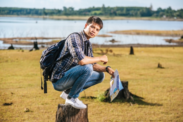 地図を運んで木の切り株に座っているバックパックを持つ男性旅行者。