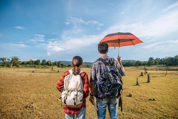男性と女性の両方の観光客が芝生の上に立っているバックパックを運びます。