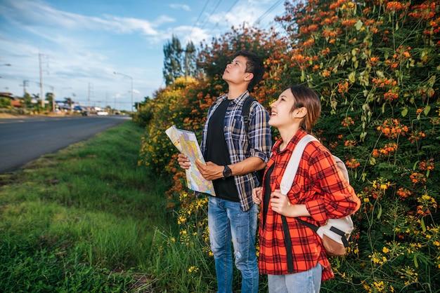 Туристы мужского и женского пола несут рюкзак, стоящий в цветочном саду. и посмотрите на вершину