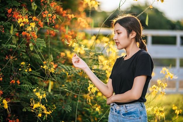 女性観光客が立ち、庭の花をキャッチします。