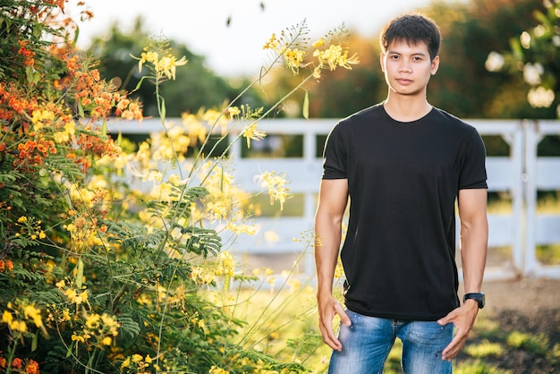 Мужчина-путешественник носит черную рубашку и стоит в цветочном саду.