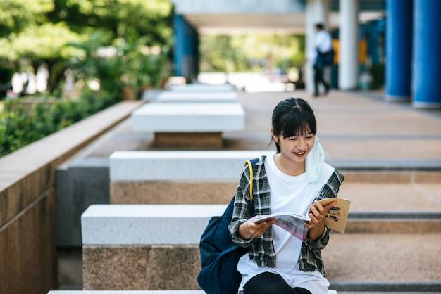 階段に座って本を読む女子学生。