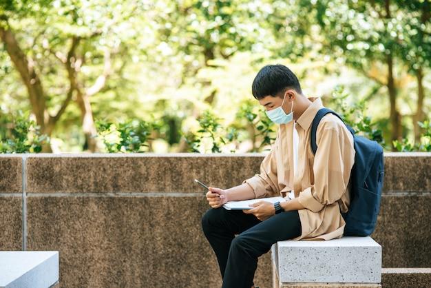 マスクをかぶった男性が階段で本を読んで座っています。