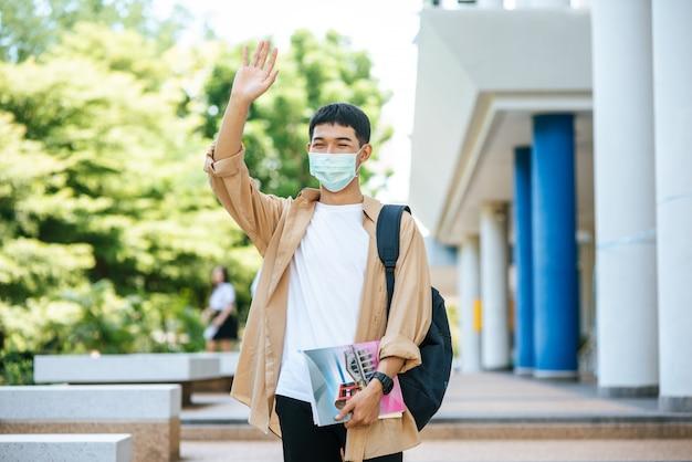 男性はマスクを着用し、本を持ち、階段にバックパックを持ちます。