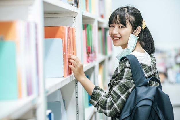 バックパックを背負って図書館で本を探している女性。