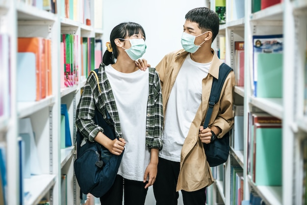リュックを背負って図書館で本を探す男女。