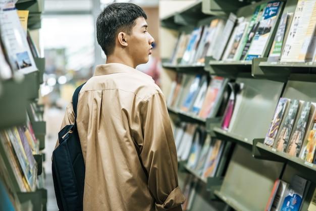 バックパックを背負って図書館で本を探している男性。