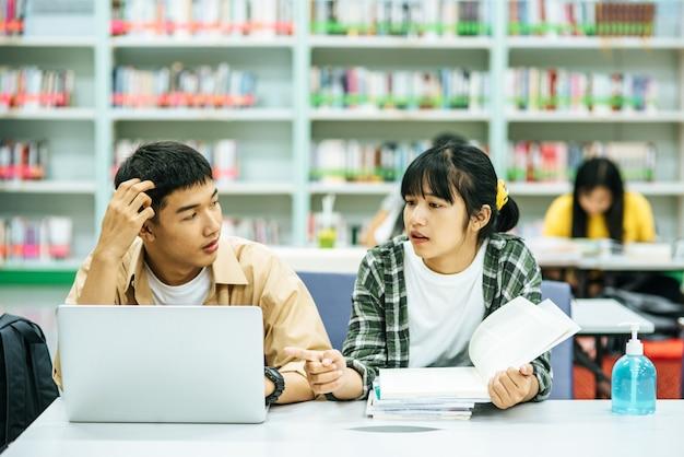 女性は本を読み、男性はラップトップを使用して図書館で本を検索します。