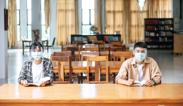 マスクをかぶった男女が図書館に座って読んでいます。